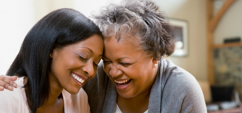 African American mother daughter heads together laughing