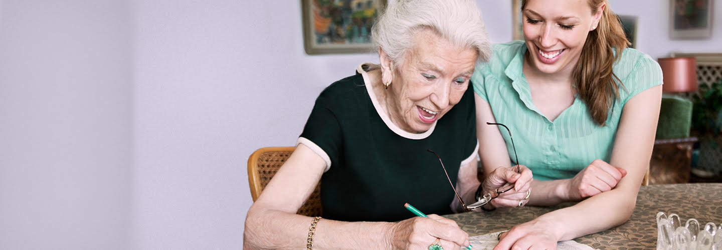 Caregiver helping elder woman with a crossword puzzle