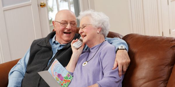 an elder couple on the phone smiling