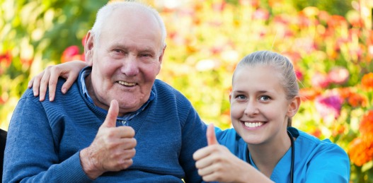 Elderly man and caregiver giving thumbs up