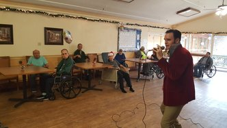 adult man singing into microphone at elderly home