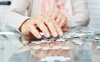 Elderly hands putting together a puzzle.