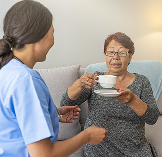 An in-home care nurse and her patient enjoying a cup of tea.