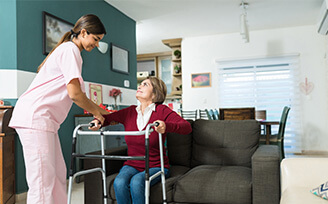 Home nurse helping an elderly woman stand up