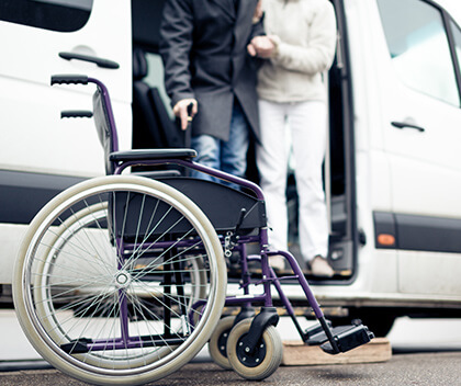 An elderly person gets help from their van to a wheelchair